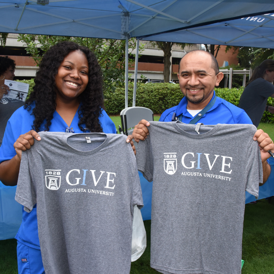 Staff holding up IGive Tshirts