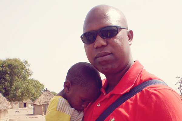 James holds a sleeping child in a village in Senegal